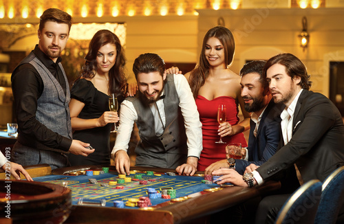 Fotografie, Obraz  Friends make bets gambiling at the roulette table in the casino.