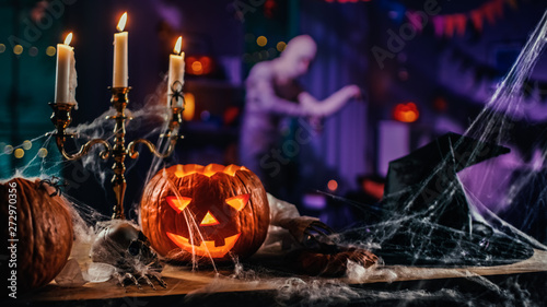Fotografia  Halloween Still Life Colorful Theme: Scary Decorated Dark Room with Table Covered in Spider Webs, Burning Pumpkin, Candlestick, Witch's Hat and Skeleton