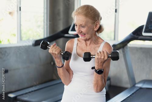 Fotografie, Obraz  Senior woman exercise lifting dumbbell in fitness gym.