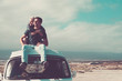 Travel people concept with young couple of man and woman sitting on the roof of old vintage van - love and relationship for travelers - beautiful landscape background