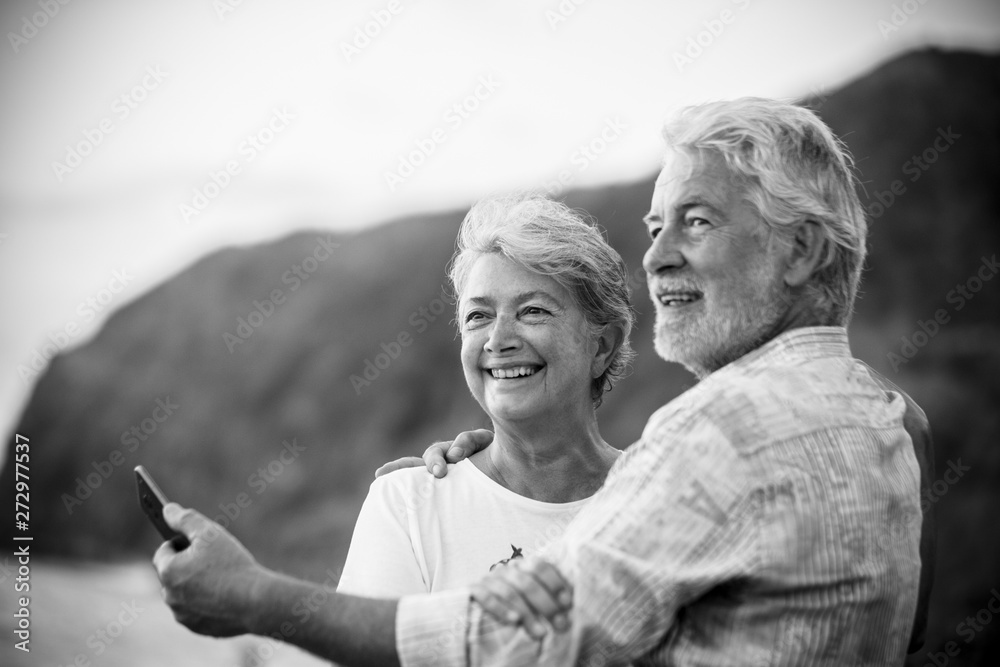 Fototapeta Beautiful romantic portrait of senior happy couple smile and hug eachother with love - forever together concept and active elderly happy lifestyle - white clear background and people smiling