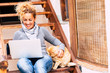 canvas print picture - Cheerful pretty middle age woman work with laptop computer outdoor at home with nice cat near her - leisure technology activity and alternative office work lifestyle for independent people