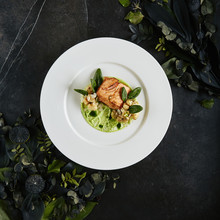 Restaurant Plate With Fillet Of Salmon 48 Degrees, Green Peas Cream And Burnt Cauliflower Top View
