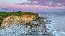 Nash Point Lighthouse, South Wales, At Sunset.  The Lighthouse Sits On The Top Of Steep Cliffs, Overlooking The Bristol Channel