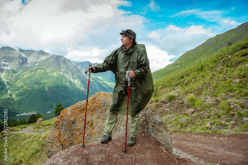 Fototapeta man tourist with backpack  trekking poles travels in the mountains obraz