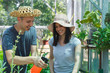 Young man and woman farmers growing organic vegetables in a greenhouse. Young farmers with hats smiling during the work in a greenhouse.