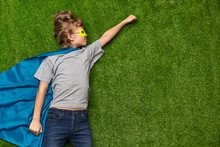 Superhero In Heroic Pose Lying On Lawn