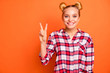 Leinwandbild Motiv Portrait of lovely sweet millennial she her make v-sign enjoy feel rejoice dressed checked shirt plaid isolated orange background