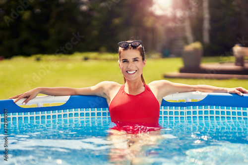 fototapeta na drzwi i meble Close up view of attractive woman relaxing on swimming pool in the backyard
