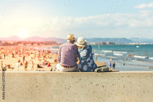 Mature couple of retired lovers enjoying retirement on the beach facing the sea with mobile cell phone taking pictures at sunset Wallpaper Mural