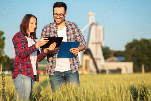 Fototapeta Two smiling happy young male and female agronomists or farmers talking in a wheat field. Woman using a tablet and man holding clipboard. Organic farming and healthy food production obraz