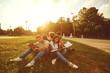 Leinwandbild Motiv Students study sitting on green grass in a park in summer spring.
