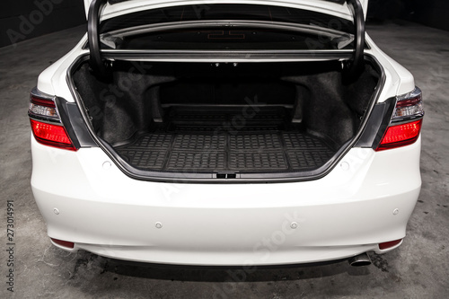 Fototapeta Close up Rear view of a  sedan white car with open trunk in garage