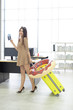 Businesswoman walking in her office.She holding passport and boarding pass as dragging yellow baggage with swim ring for travel in summer vacation.