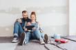 canvas print picture - junge paar macht eine pause bei der renovierung und schaut auf das tablet