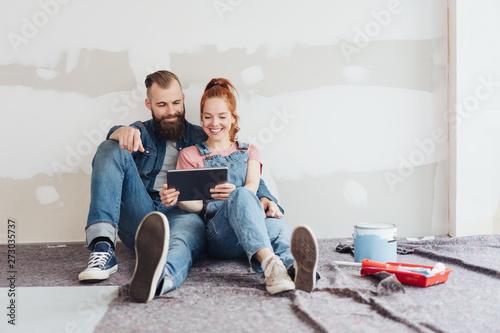 junge paar macht eine pause bei der renovierung und schaut auf das tablet Canvas Print