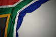 canvas print picture - waving national flag of south africa on a gray background.