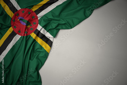 Poster Pays d Asie waving national flag of dominica on a gray background.