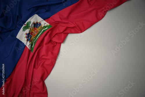 Photo waving national flag of haiti on a gray background.