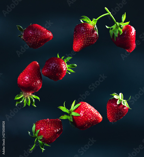 Bright and juicy strawberries thrown into the air on a black and gray background with chaotic splashes of water