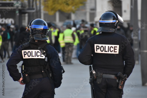 Fotografie, Obraz  Helmeted police officers photographed from behind during a protest