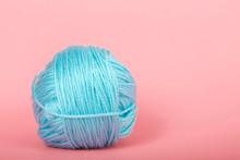 Single Ball Of Light Blue Baby Soft Thin Yarn On A Light Pink Background.