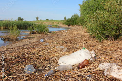 plastic bottles, bags and garbage are lying on the shore. waste, dirt, environmental pollution.