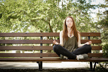 Young Woman Meditating On Park...
