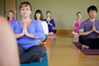 Students in yoga class sitting in hands to heart pose