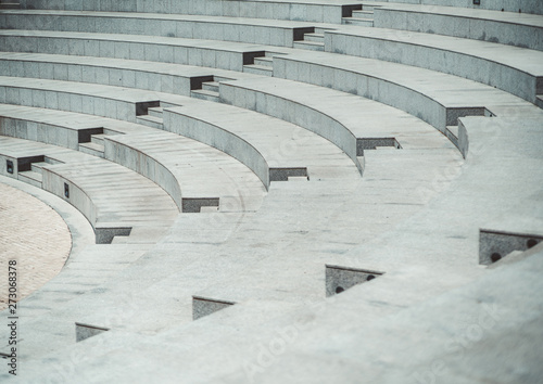 Rows of grayish stony or marble seats and flights of stairs of a modern outdoor Fotobehang