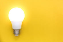 LED Light Bulb On Yellow Background, Concept Of Ideas, Creativity, Innovation Or Saving Energy, Copy Space, Top View, Flat Lay