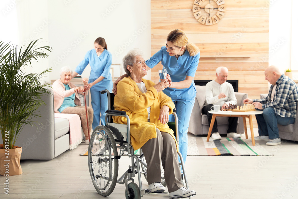 Fototapeta Nurse giving glass of water to elderly woman in wheelchair at retirement home. Assisting senior people