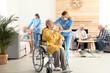 canvas print picture - Nurse giving glass of water to elderly woman in wheelchair at retirement home. Assisting senior people