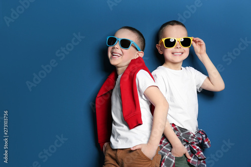 Photo Portrait of cute twin brothers with sunglasses on color background