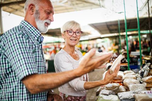 Pinturas sobre lienzo  Portrait of beautiful elderly couple in market buing food