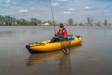 Kayak Fishing At Lake. Fisherwoman With Pike Fish On Inflatable Boat With Fishing Tackle.