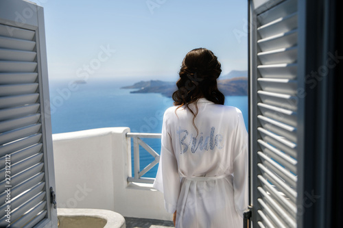 Fotografering The bride is dressed in a white robe, on the morning of her wedding day stands on a balcony overlooking the sea