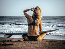 Blonde Surfer Girl Sitting In Lotus Pose At The Sand Beach With Surfboard And Looking At The Ocean Playing With Hair