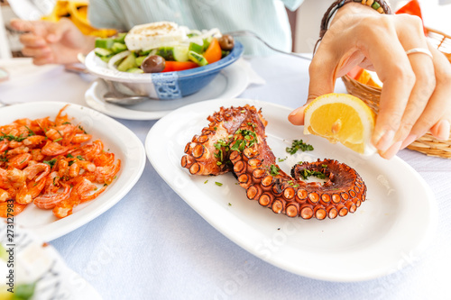 Photo  Close-up of a woman eating delicious seafood - shrimp and octopus grilled and vegetable salad
