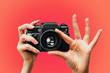 Leinwanddruck Bild - Vintage Camera in female hand. A photo. Photographer. Manual focus. Colored background. Red