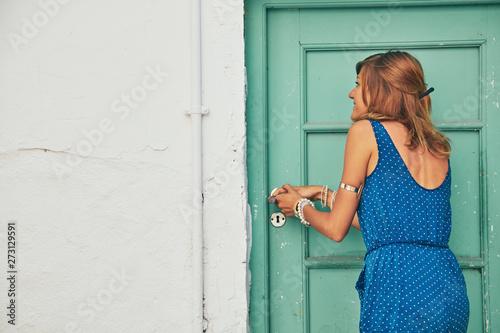 Fotografía  Girl entering at the old retro vintage house door.