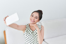 Happy Young Woman Taking Selfie With Her Cellphone While Sitting At Living Room