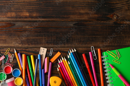 Fotografía  Flat lay composition with school supplies on wooden background, space for text