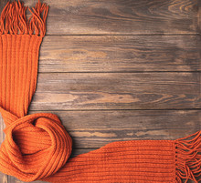 A Bright Knitted Orange Knitted Scarf On A Wooden Background. Horizontal Frame. Flat Layout. Autumn Concept