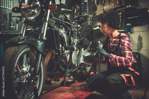 African american woman mechanic repairing a motorcycle in a workshop