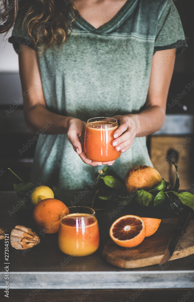 Fototapeta Young female holding glass of freshly squeezed blood orange juice or smoothie in hands near concrete kitchen counter. Healthy lifestyle, vegan, vegetarian, alkaline diet, spring detox concept