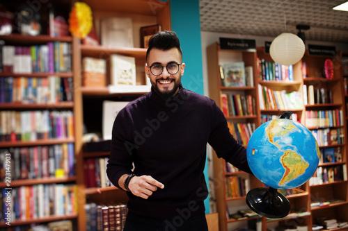 Fotografie, Tablou  Tall smart arab student man, wear on violet turtleneck and eyeglasses, at library holding earth globe at hands