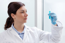 Young Female Scientist Looking At A Test-tube Containing Blue Liquid