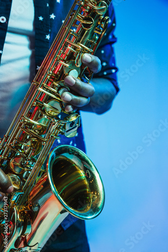 Young african-american jazz musician playing the saxophone on blue studio background in trendy neon light Canvas Print