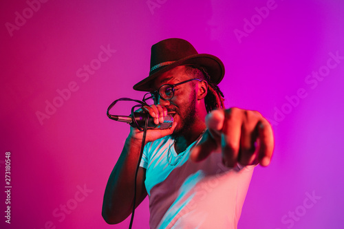 Obraz na plátně Young african-american jazz musician with microphone singing a song on purple studio background in trendy neon light